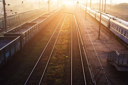 railways with freight and passenger trains beautifully lit by setting sun