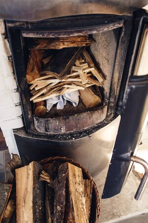 Composition, firewood, stove items, basket. A real fireplace filled with firewood