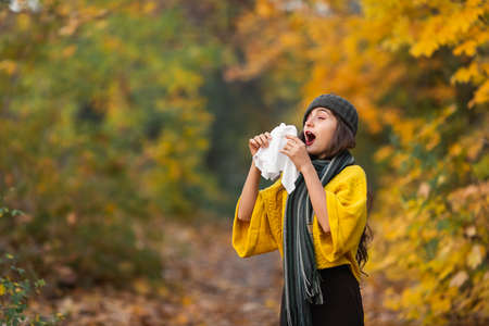 girl sneezes into a headscarf in autumn in the park. allergy or viral infection concept.