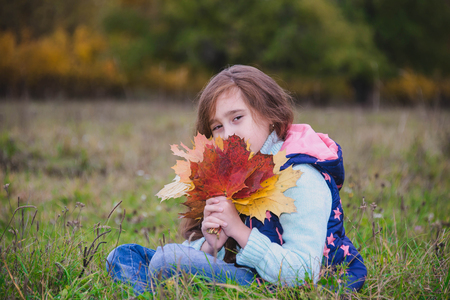 autumn baby with a bunch of leaves