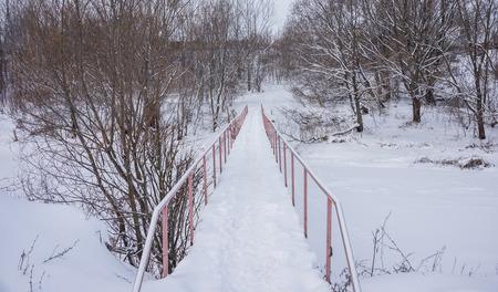 a small bridge over the river in the winter, to move people Banco de Imagens