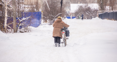 the woman with the bike is in winter, along the road