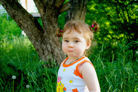 a curious child, outdoors, surprise emotions, in the summer on the grass Stock Photo