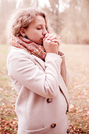 pregnant girl on a walk in the Park, late autumn, warm breathing hands Stock Photo