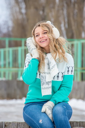 girl with curly hair , in green sweater , with mittens, smiling