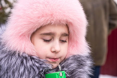 the child drinks juice at the festival, seeing the Russian winter