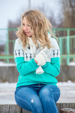girl with curly hair in a green sweater, mittens and headphones, outdoor portrait Standard-Bild - 96392743