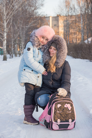 a young mother leads her daughter from school, the family smiles, children have fun, the family walks in the winter, go on the road. Stock Photo