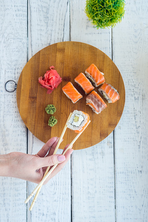 rolls, traditional Japanese cuisine, delicious healthy food, eating with chopsticks, eating with a tray