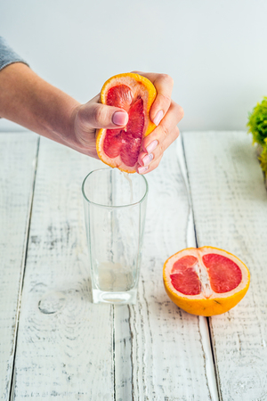 freshly squeezed grapefruit juice in glass glass Fougeres in the hands of a girl with beautiful nails and manicure, healthy lifestyle