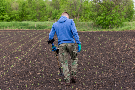 man to seek treasure on earth with a metal detector, walks the field, squeak gold