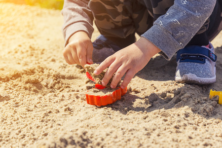 hands of the child in the sand, the child plays in the sand with a red spatula