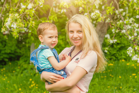 mother and child in nature in the Park, resting on the green grass in Sunny weather, happy family