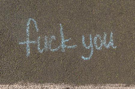 chalk inscription, fuck you, the inscription on the asphalt in large letters Banco de Imagens
