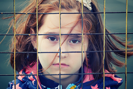 abandoned child, children without parents, social problems of the population, raising children in shelters, homeless people, people behind bars, artistic photo retouching Foto de archivo