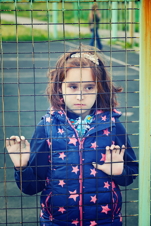 abandoned child, children without parents, social problems of the population, raising children in shelters, homeless people, people behind bars, artistic photo retouching Stock Photo