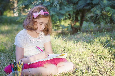 little girl draws with pencils in an album while sitting on the grass in a park in nature