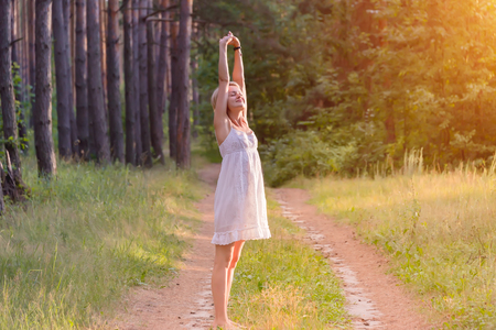 beautiful pregnant girl in the forest raises her hands to the sky