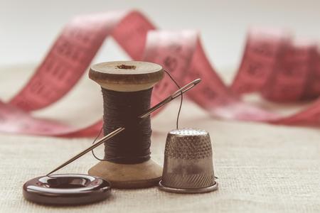 la composizione della sarta, del sarto, del filo per cucire e per maglieria, del filo grigio e dell'ago e del bottone Archivio Fotografico