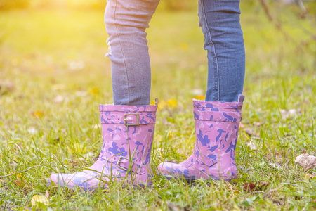 childrens feet in rubber boots on yellowed dry grass in autumn Stock Photo