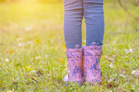 children's feet in rubber boots on yellowed dry grass in autumn