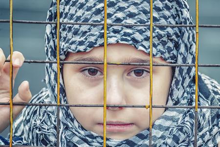 niña refugiada llorando del este con un pañuelo en la cabeza Foto de archivo