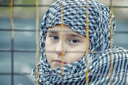 crying refugee girl from the east in a headscarf Imagens