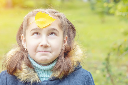 girl with yellow leaves on her face. smiles 版權商用圖片