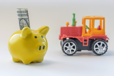 piggy bank with inserted dollar on the background of the tractor. concept of financial investment in agriculture.