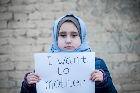 refugee girl with an inscription on a white sheet i want to mother Stok Fotoğraf