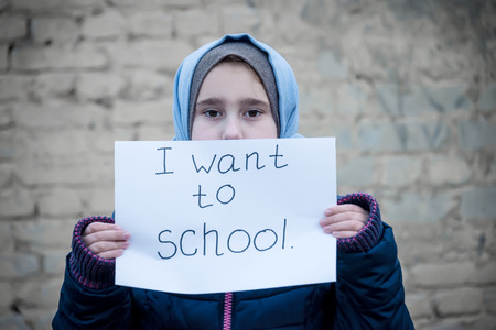 refugee girl with an inscription on a white sheet