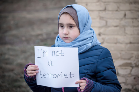 "refugee girl with an inscription on a white sheet ""i not a terrorist"""
