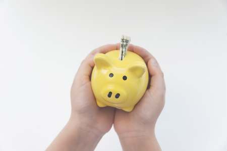 yellow pig moneybox in the hands of a child. one dollar. White background 版權商用圖片