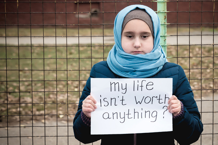refugee girl with the inscription on a white sheet