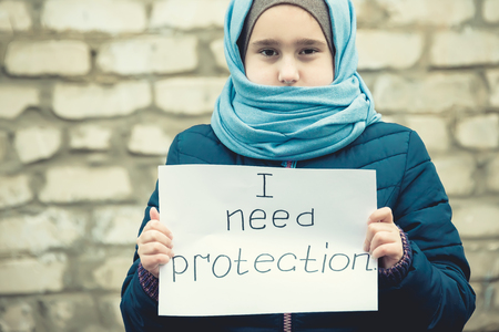 "refugee girl with an inscription on a white sheet ""i need protection"""