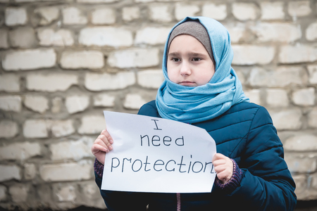 """ragazza rifugiata con un'iscrizione su un foglio bianco """"ho bisogno di protezione"""""""