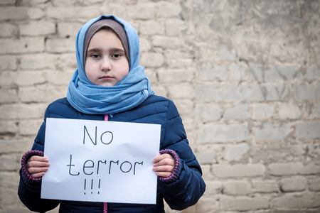 "refugee girl with an inscription on a white sheet ""no terror"""