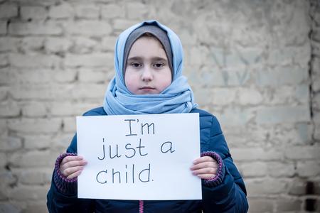 ragazza rifugiata con un'iscrizione