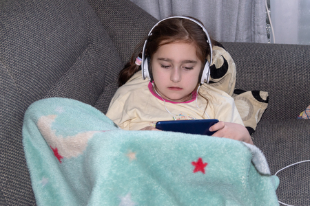 girl in headphones playing in the phone, lying on the sofa, the concept of childish play addiction, natural photo