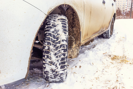 dirty automobile wheel in the winter by white car