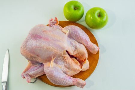 Fresh chicken carcass lies on the table on a white background. chicken carcass with green apples and knife.