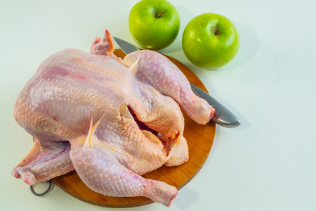 Fresh chicken carcass lies on the table on a white background. chicken carcass with green apples and knife. Archivio Fotografico - 125148581