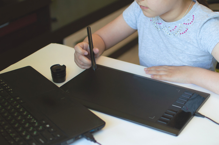 child girl draws on a graphic tablet while sitting at a table with a laptop Archivio Fotografico - 125150357