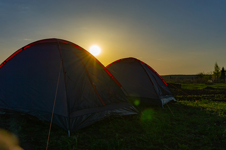 two tourist tents on the grass in the evening at sunset in travel Archivio Fotografico - 125136574