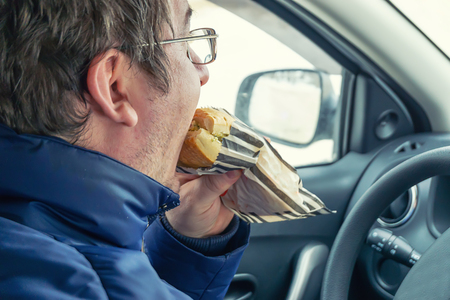 the adult man wearing spectacles eats sandwich in the car the rear view Archivio Fotografico - 125135545