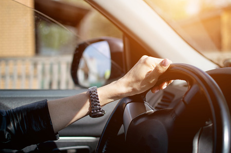female hand with a clock. female hands on the steering wheel in the car. Archivio Fotografico - 125133010