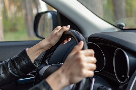 female hand with a clock. female hands on the steering wheel in the car.