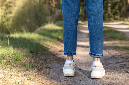 female legs in white sneakers and jeans on a footpath in the summer forest Archivio Fotografico - 125132833