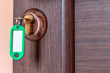 a brown door with a key in it with a green tag Reklamní fotografie