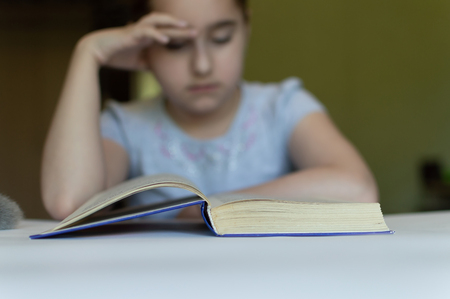 tortured girl child reads a book at the table and she is very tired and wants to sleep, yawns, falls asleep while reading stories and lessons Archivio Fotografico - 125132706